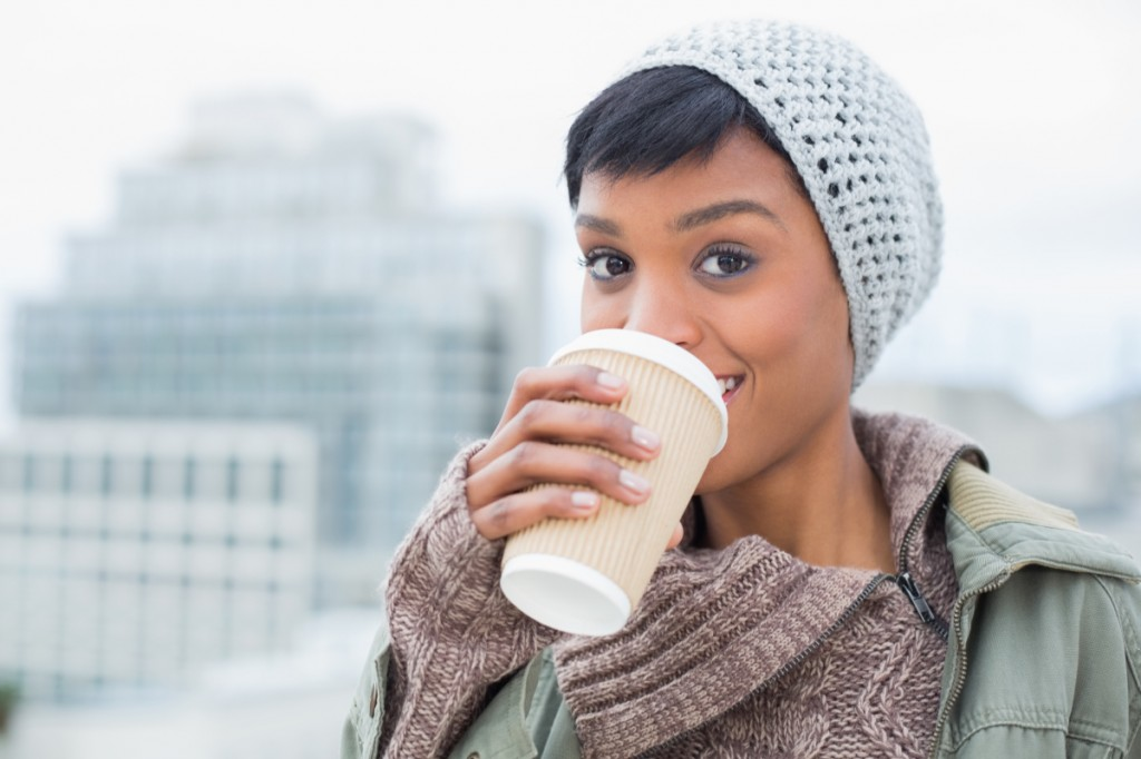 Happy young model in winter clothes enjoying coffee outside on a